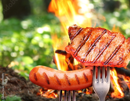 Sausage and steak on a fork.