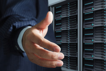 business man offers handshake in server room