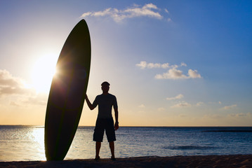Silhouette of man with paddle board