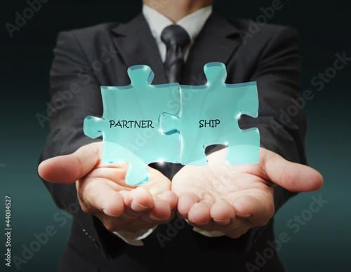 """businessman shows """"3d partnership"""" written puzzle pieces"""