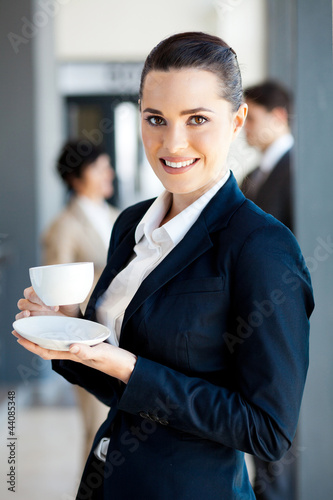 beautiful young businesswoman drinking coffee in office