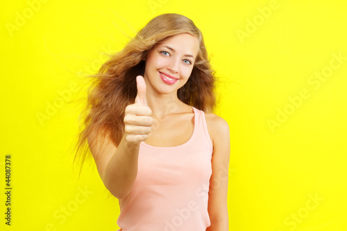 Portrait of attractive girl showing a thumbs up on yellow backgr