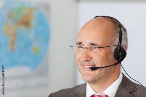 geschäftsmann mit headset vor einer landkarte