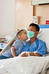 a patient and son with saline intravenous (iv) on hospital bed
