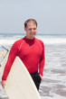 man the surfer to stand on a beach on an ocean coast