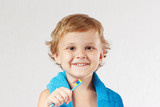 Young cute blond boy with toothbrush with pink toothpaste