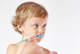 Young cute blond boy brushing his teeth