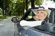 Junge blonde Frau mit Hut im Cabrio