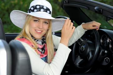 Attraktive  Frau mit Sommerhut im Cabriolet