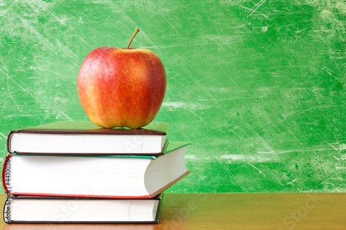 books with apple against dirty chalkboard