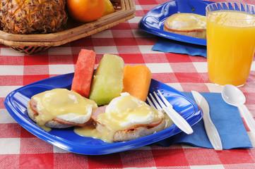 Eggs Benedict with fresh melon slices