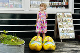 Little girl in giant wooden yellow clogs
