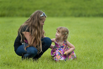 Happy teenage girl and a toddler in the grass