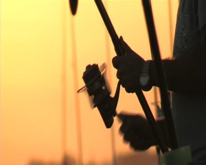 Fisherman recovering fishing line at sunset. 16 9.