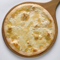 Pizza ai quattro formaggi intera su pala di legno