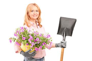 Female gardener holding  flowers and a shovel