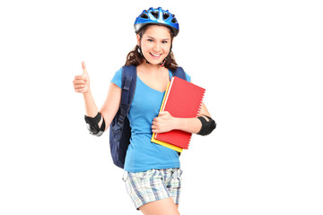 Girl on rollers holding notebooks and giving thumb up