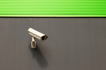Security camera on a building with green facade