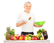 Mature man eating a salad with fruits and vegetables on a table