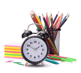 Alarm clock, notebook stack and pencils. Schoolchild and student