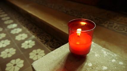 Illuminated candle in a church