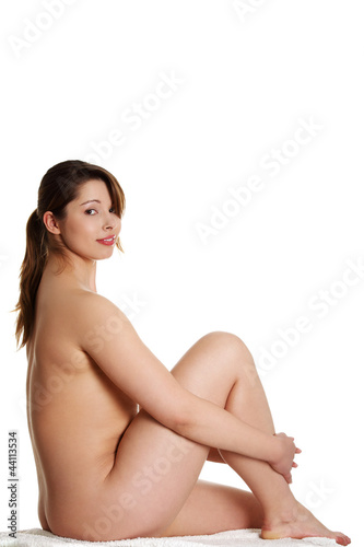 Nude overwieght woman is sitting and smiling.