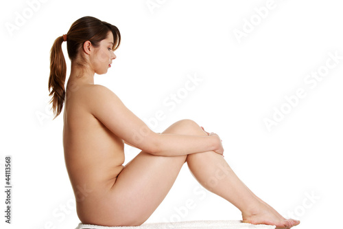 Nude overwieght woman is sitting with hands on knee.