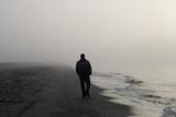 Fototapety Lonely man walking on a beach