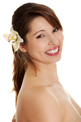 Naked woman with orchid flower in hair is smiling.