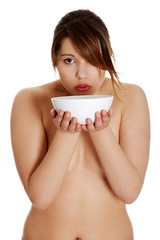 Naked woman is drinking from white bowl.