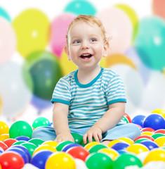 Cute boy playing colorful balls
