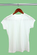White t-shirt on hanger on green background
