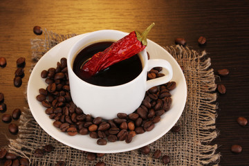 Coffee and pepper on wooden table on brown background