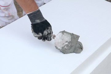 Trowel spreading mortar styrofoam insulation of wall
