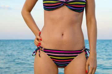 Beautiful female body in striped bikini
