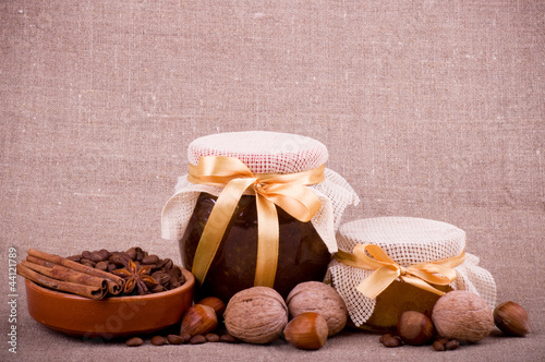 Tasty jam, clay pot and nuts on background