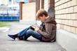 School teen with electronic tablet sitting