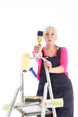 Female decorator wearing dungarees on a ladder