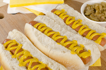 Simple Hot Dogs with yellow mustard and caramelized onions.