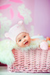 newborn baby girl in pink knitted bear hat lies at basket