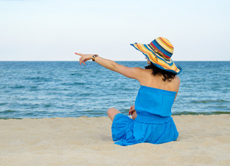 Woman pointing to the ocean