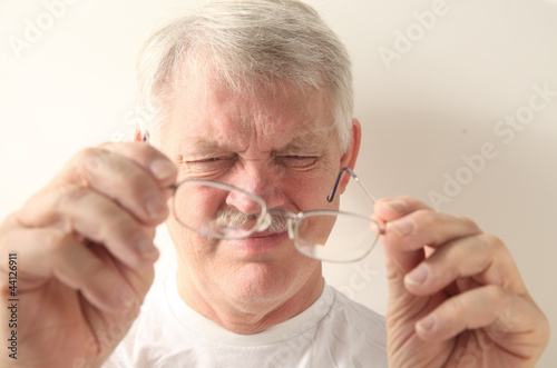 an older man squints at his glasses