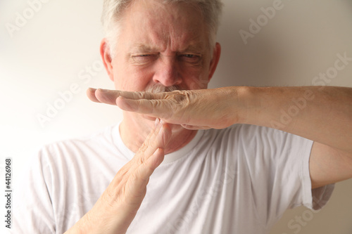 an older man gives the timeout gesture