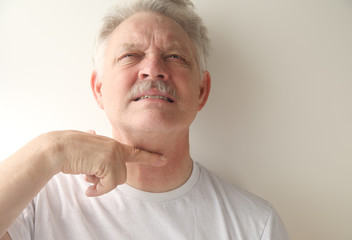 an older man gives the cutthroat signal