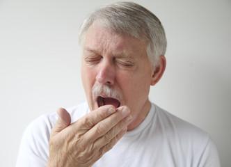 senior man getting ready to yawn or sneeze