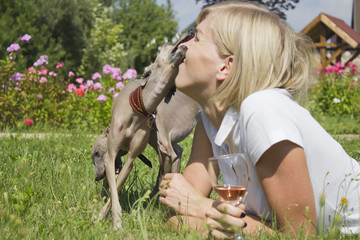 Young woman with dog and glass of wine