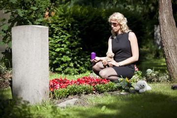 junge Mutter trauert mit Kerze und Teddy am Grab vom Kind