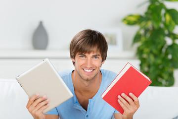 lächelnder mann zeigt buch und tablet