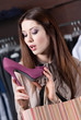 Woman scrutinizes elegant fuchsia shoes at the store