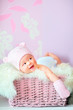 smiling newborn baby girl in pink hat and mittens at basket